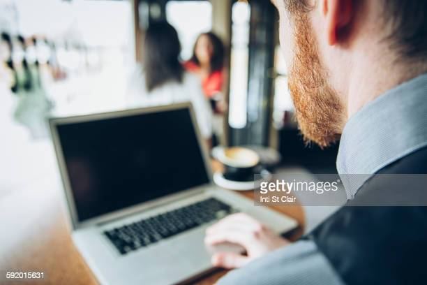 Caucasian businessman using laptop in cafe