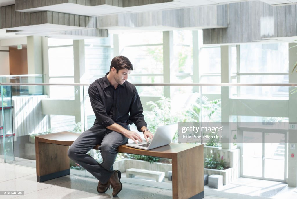 Caucasian businessman using laptop in office lobby : Stock Photo