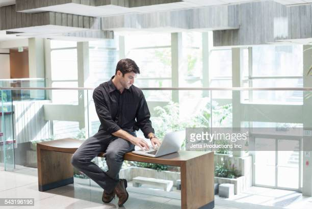 Caucasian businessman using laptop in office lobby