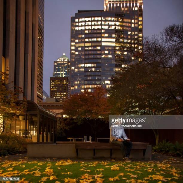 Caucasian businessman using laptop in urban courtyard