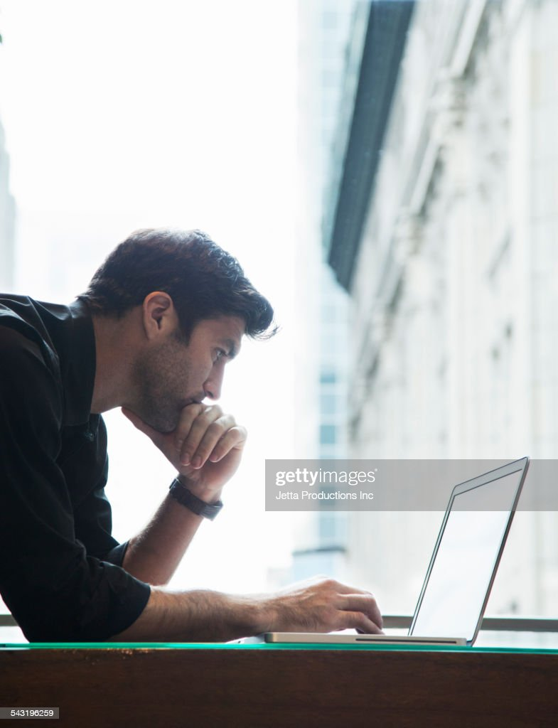 Caucasian businessman using laptop near window : Stock Photo