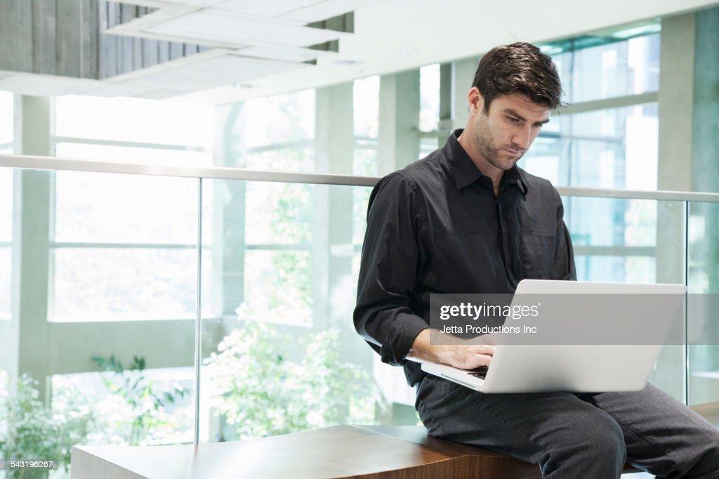 Caucasian businessman using laptop on bench : Stock Photo