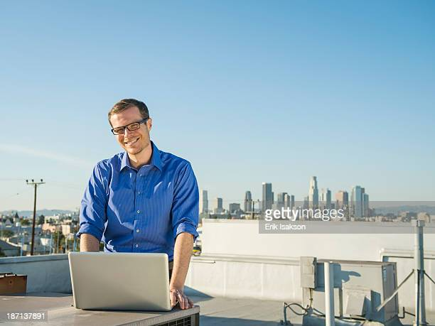 Caucasian businessman using laptop on urban rooftop