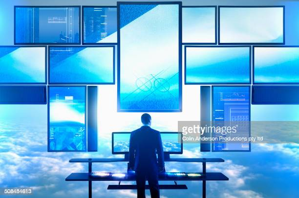 Caucasian businessman using multiple screens at desk in clouds