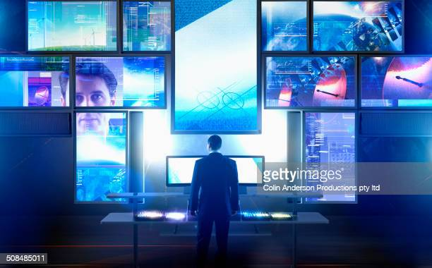 caucasian businessman using multiple screens at desk - spionage und aufklärung stock-fotos und bilder