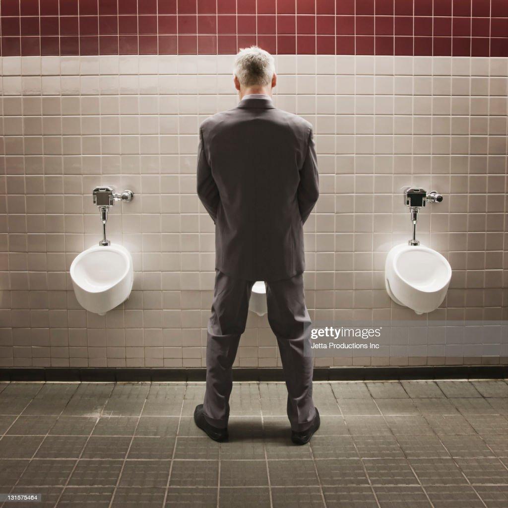 Caucasian businessman using public restroom : Stock Photo