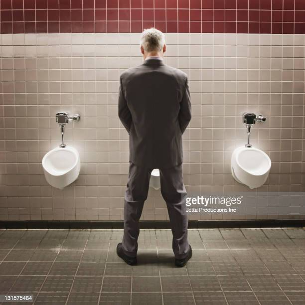 Caucasian businessman using public restroom