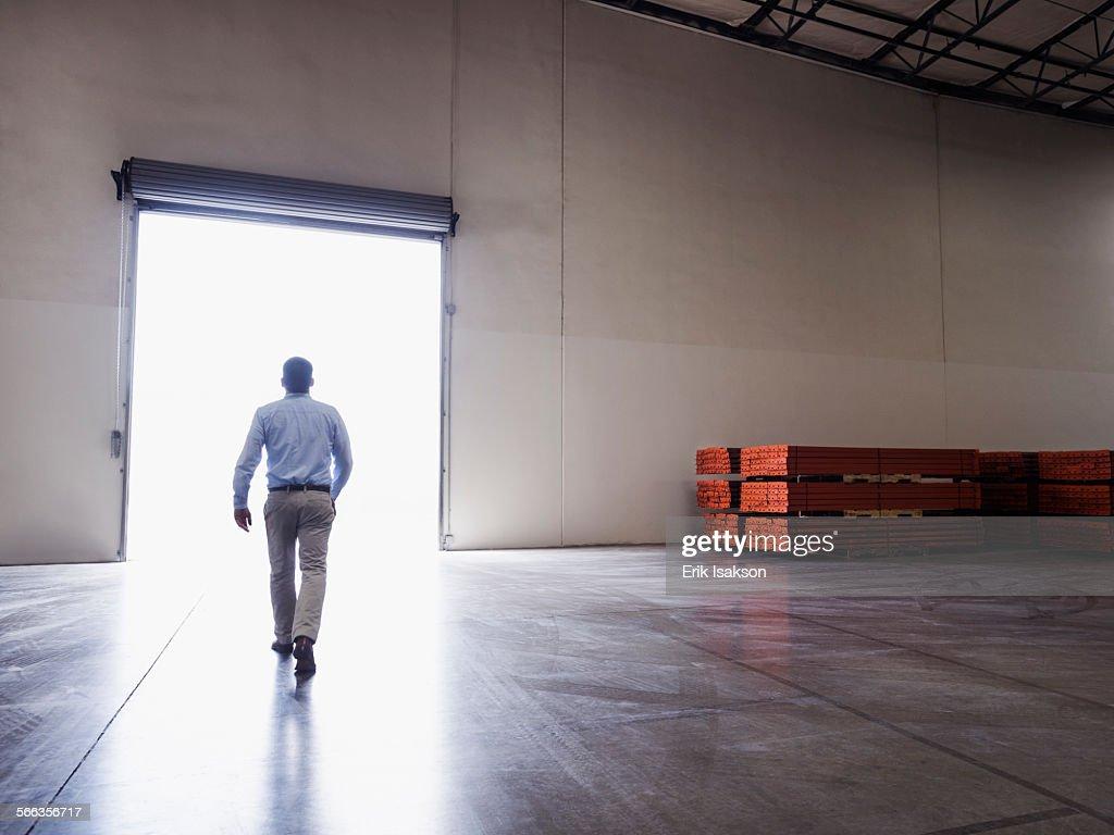 Caucasian businessman walking in warehouse : Stock Photo
