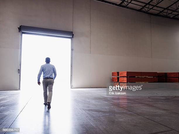 Caucasian businessman walking in warehouse
