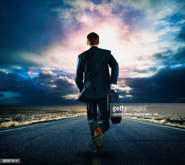 Caucasian businessman walking on remote road under cloudy sky