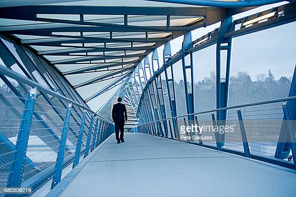 Caucasian businessman walking on sky bridge