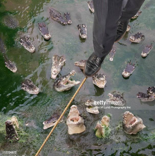 Caucasian businessman walking tightrope over alligators