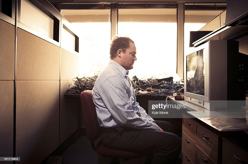 Caucasian businessman watching television at desk : Stock Photo