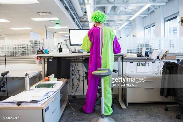 caucasian businessman wearing clown costume in office - clown stock-fotos und bilder