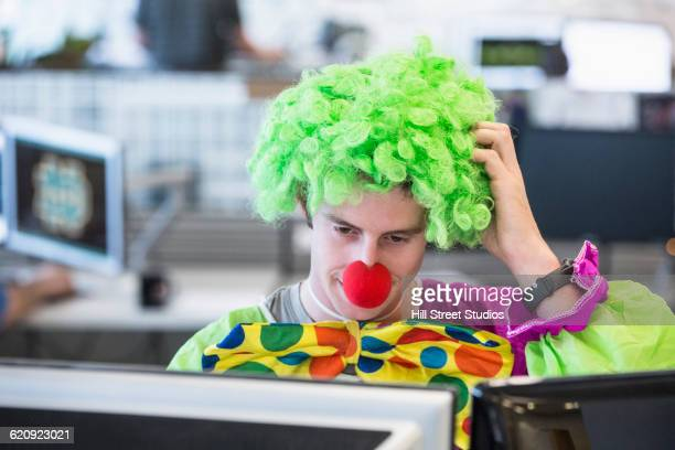 caucasian businessman wearing clown costume in office - clown stock photos and pictures