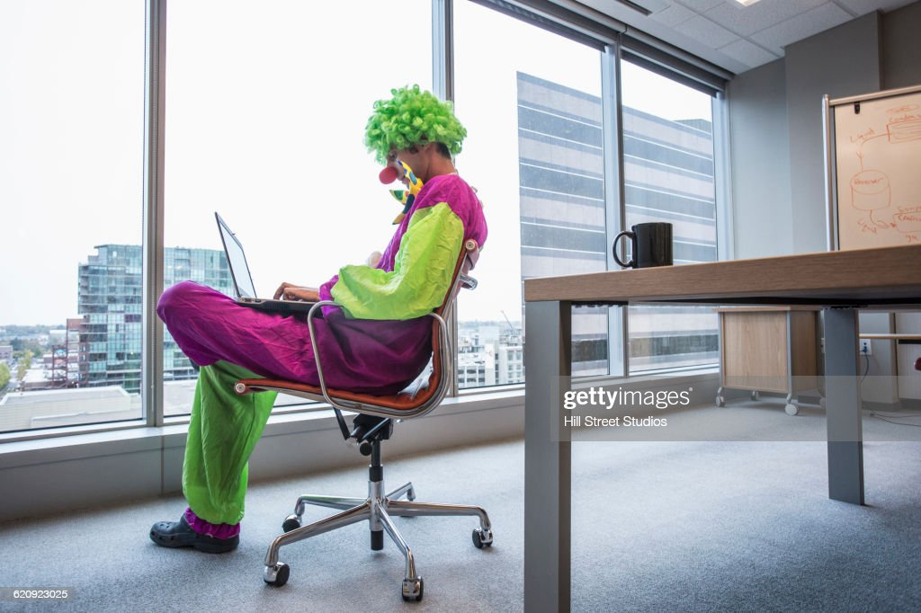 Caucasian businessman wearing clown costume in office : Stock Photo