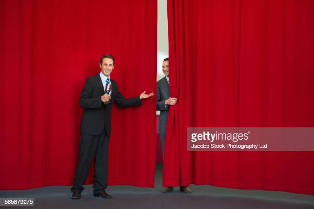 Caucasian businessman welcoming colleague on stage