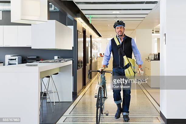 Caucasian businessman with bicycle in office
