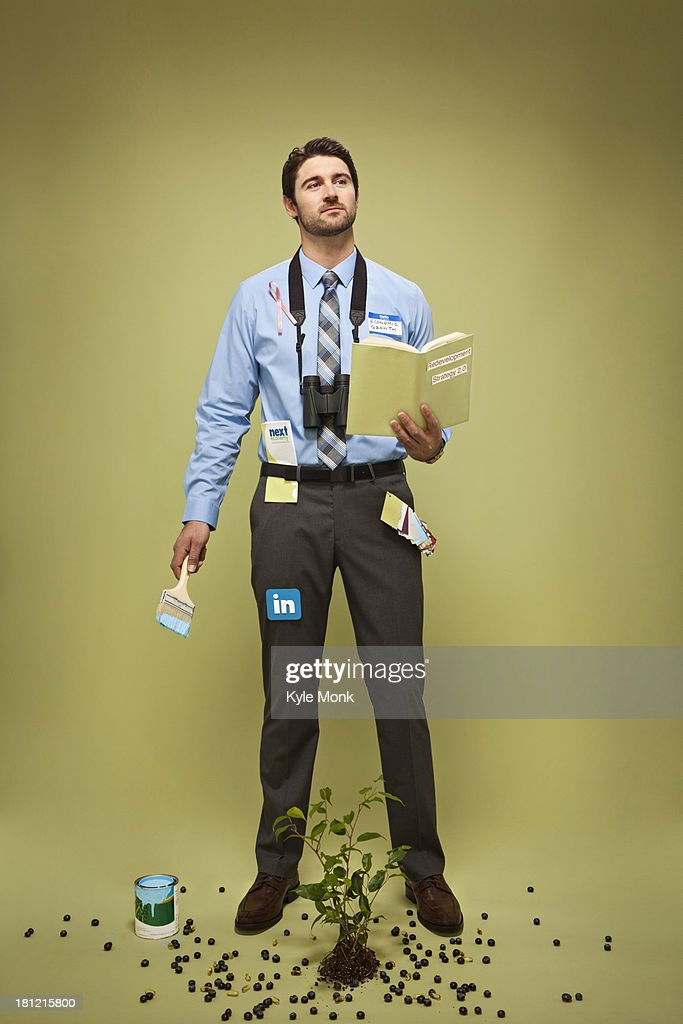 Caucasian businessman with book, pot of paint, plant and binoculars : Stock Photo