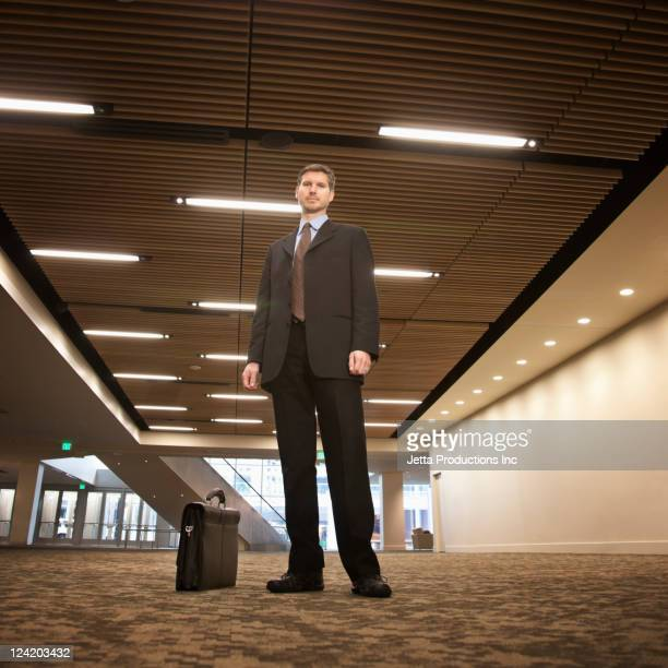 Caucasian businessman with briefcase in hotel