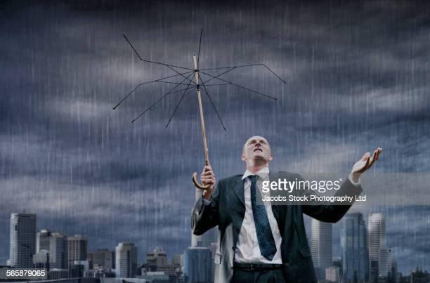 Caucasian businessman with broken umbrella standing in rain storm