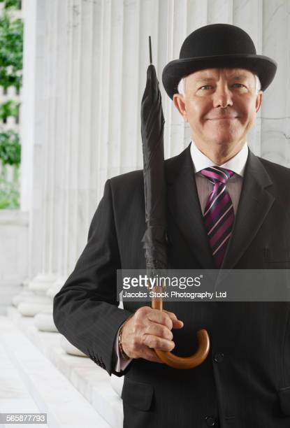 Caucasian businessman with derby carrying umbrella