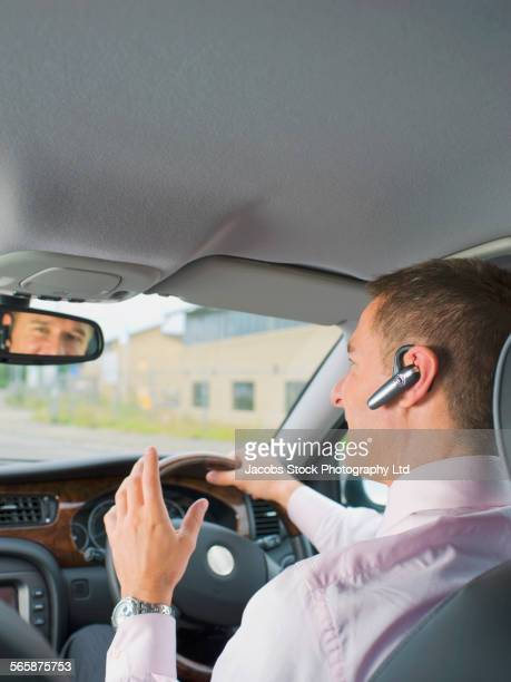 Caucasian businessman with headset driving car