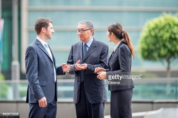 Kaukasische Geschäftsmann mit seinem Dolmetscher einen Deal mit senior asiatischen Geschäftsmann zu diskutieren