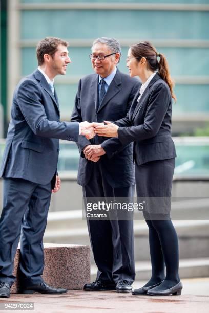 上級アジアのビジネスマンとの取引を議論する彼の通訳と白人実業家