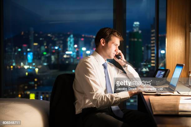 Caucasian businessman working late in hotel room