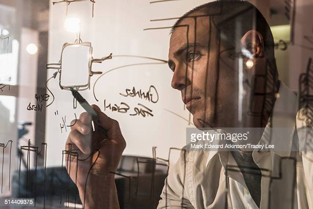 Caucasian businessman writing on glass