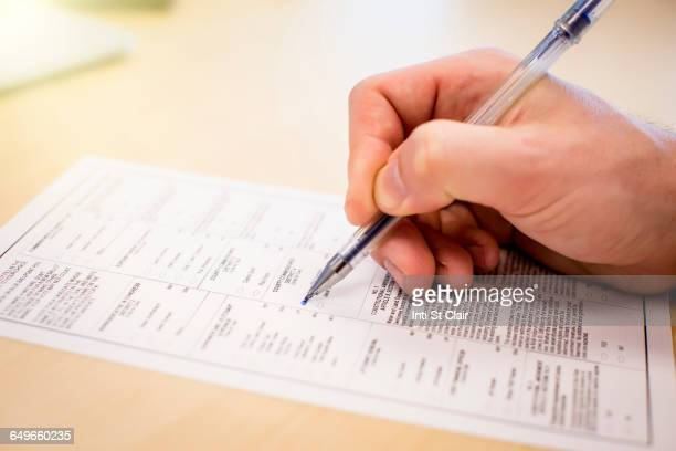 caucasian businessman writing paperwork - voter registration stock pictures, royalty-free photos & images