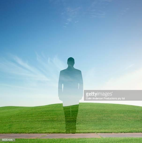 Caucasian businessman's silhouette over rural landscape