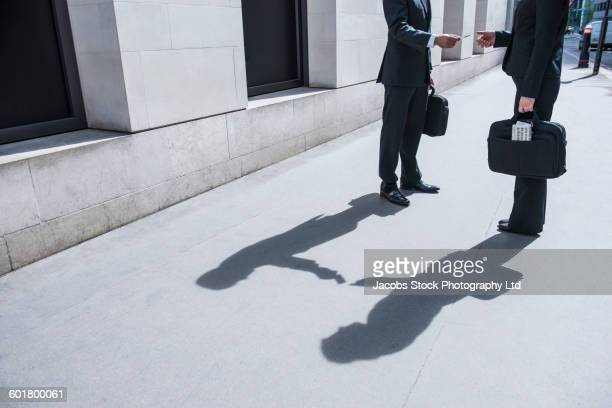 Caucasian businessmen exchanging business cards