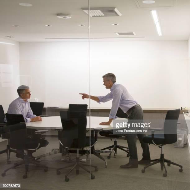 caucasian businessmen having meeting in office - もがく ストックフォトと画像