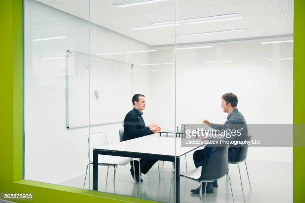 Caucasian businessmen playing table tennis in office meeting