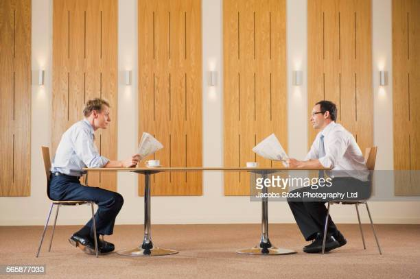Caucasian businessmen reading newspapers at table
