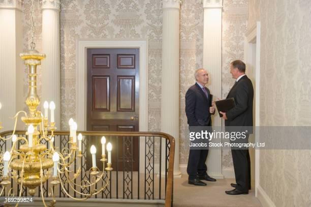 caucasian businessmen talking in ornate hallway - formelle geschäftskleidung stock-fotos und bilder