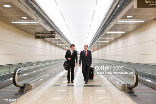 Caucasian businessmen walking in airport