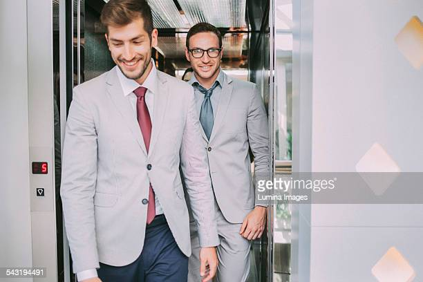 Caucasian businessmen walking out of elevator
