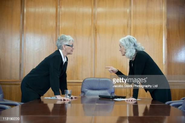 Caucasian businesswoman arguing in conference room