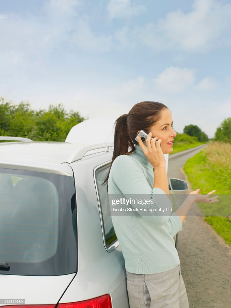 Caucasian businesswoman calling for help from broken down car on rural road : Stock Photo