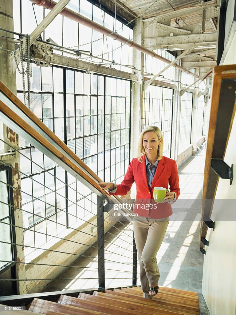 Caucasian businesswoman carrying cup of coffee on warehouse staircase : Stock Photo