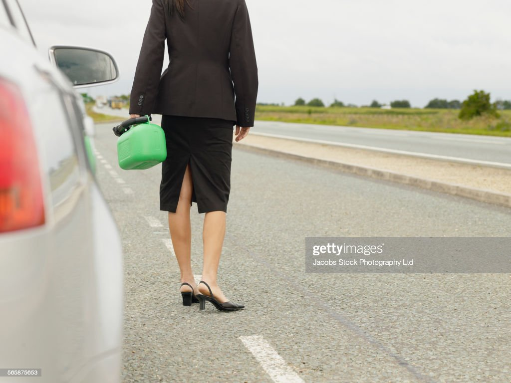 Caucasian businesswoman carrying gasoline can on rural road : Stock Photo