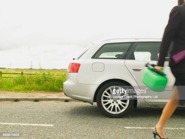 Caucasian businesswoman carrying gasoline can on rural road