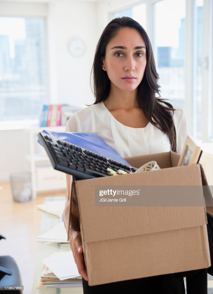 Caucasian businesswoman carrying personal items : Stock Photo