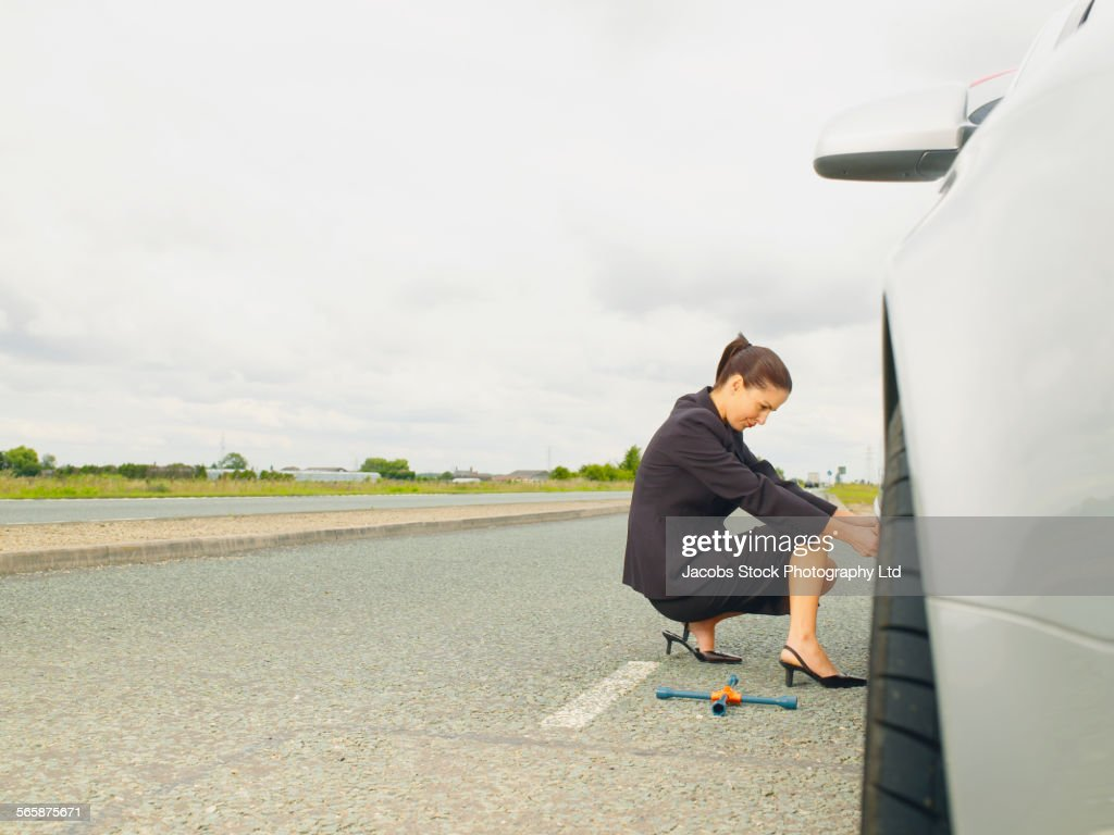 Caucasian businesswoman changing car tire on rural road : Stock Photo