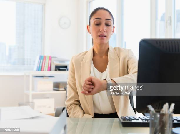 Caucasian businesswoman checking watch at desk