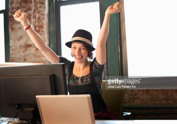 Caucasian businesswoman cheering at desk in office