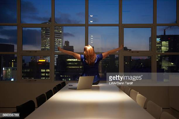 Caucasian businesswoman cheering at laptop in office at night